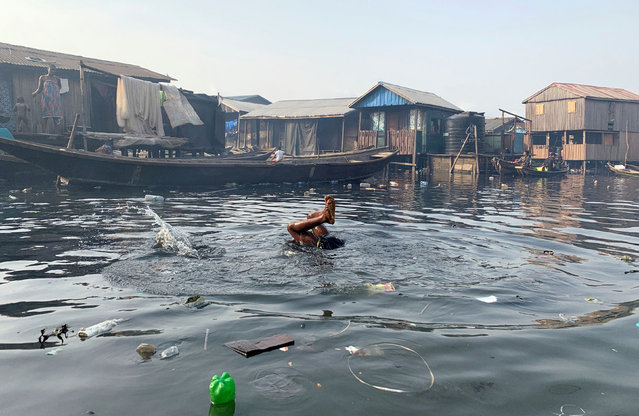 A boy swims in the polluted water of the Makoko community in Lagos, Nigeria on March 9, 2020. (Photo by Temilade Adelaja/Reuters)