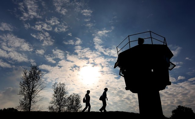 Visitors walk along a watchtower of the former German Democratic Republic (GDR) in Hoetensleben, eastern Germany, on October 2, 2014. This year Germany marks the 25th anniversary of the fall of the German-German border, that fell in November 1989. (Photo by Ronny Hartmann/AFP Photo)