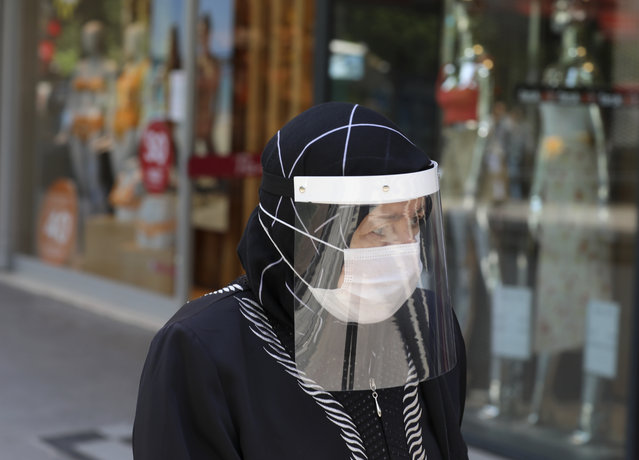 A woman wearing a face mask and a shield to protect against the spread of coronavirus, walks in the city's historical part of Ulus, in Ankara, Turkey, Thursday, June 18, 2020. Turkish authorities have made the wearing of masks mandatory in three major cities to curb the spread of COVID-19 following an uptick in confirmed cases since the reopening of many businesses. (Photo by Burhan Ozbilici/AP Photo)