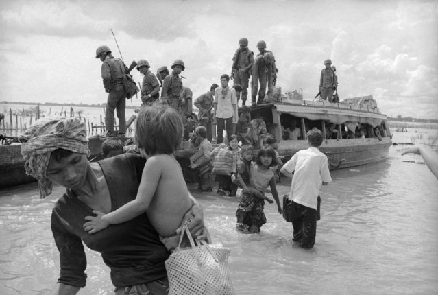 Residents of Kompong Cham, the Cambodian provincial capital near Phnom Penh, arrive on the Eastern Bank of the Mekong River as they flee fighting September 21, 1973. Soldiers in background were being transported simultaneously to defend the hamlet of Tonle Bet against attacks by Khmer Rouge insurgents. (Photo by Chor Yuthy/AP Photo)