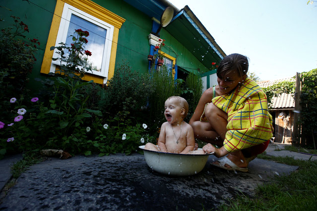 "Ekaterina, granddaughter of 75-year old Ekaterina Panchenya, bathes her daughter Dasha in a basin on a hot summer day. It was ""cars, noise and dirt"" and the sight of city dwellers standing in line to buy groceries that dissuaded her from leaving Pogost. (Photo by Vasily Fedosenko/Reuters)"