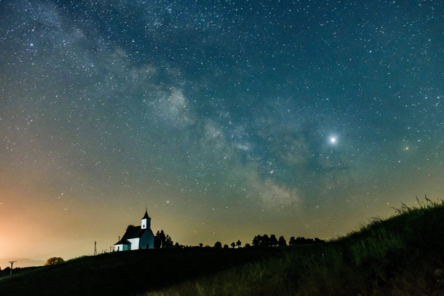 The Milky Way galaxy and the Jupiter (bottom R) are pictured near Gemersky Jablonec, Slovakia, early 08 June 2019. (Photo by Peter Komka/EPA/EFE)
