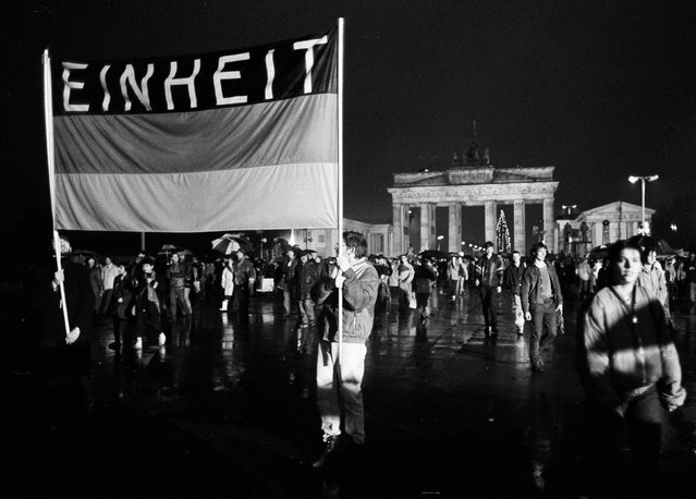 People hold a German flag with the word reading 'Unity' as they cross the newly opened checkpoint between East and West Berlin at the Brandenburg Gate, December 22, 1989. (Photo by Fabrizio Bensch/Reuters)