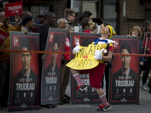 An anti-NDP demonstrator walks in front of supporters for Liberal leader Justin Trudeau before the start of the French language leaders' debate in Montreal, Quebec October 2, 2015. Canadians go to the polls in a federal election on October 19, 2015. (Photo by Christinne Muschi/Reuters)