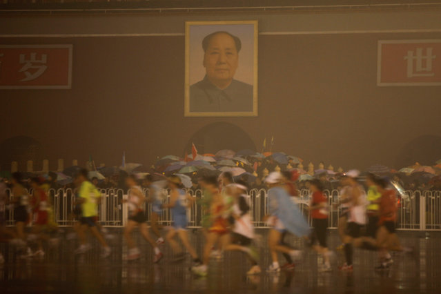 Participants run past the Tiananmen Gate in front of the portrait of late Chinese leader Mao Zedong during the 2010 Beijing Marathon on a rainy day in Beijing October 24, 2010. (Photo by Grace Liang/Reuters)