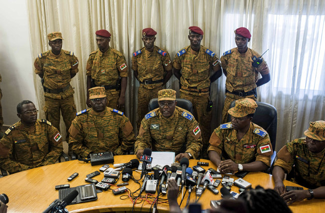 Burkina Faso's new interim leader Gen. Honore Nabere Traore, third from left in front, speaks during a press conference held in Ouagadougou, Burkina Faso, Friday, October 31, 2014. President Blaise Compaore stepped down Friday, pushed from power in Burkina Faso after 27 years by a burst of violent protests that set the parliament ablaze and refused to accept anything short of resignation. (Photo by Theo Renaut/AP Photo)