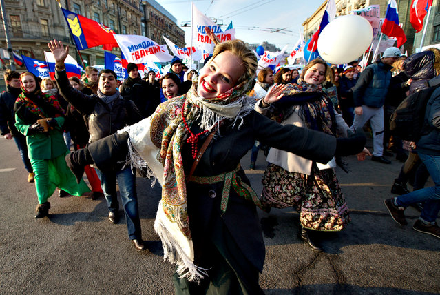 People of pro-government groups, with Russian flags, dance marching through downtown Moscow to mark People s Unity Day, a public holiday, in Russia, on Tuesday, November 4, 2014. (Photo by Ivan Sekretarev/AP Photo)