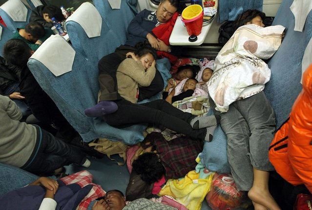 People sleep on their seats on the train from Guangzhou to Changchun to go back home for the Lunar New Year, or Spring Festival, on February 6, 2013. Passengers will log 220 million train rides during the 40-day travel season as they criss-cross the country to celebrate with their families, but just as making the trip home can be laborious – often lasting one or two days – so can simply acquiring a seat on the train, and every year complaints arise about the inefficiency or unfairness of the system, although an initiative allowing travelers to purchase tickets online aims to curb long queuing times. (Photo by China Photo Press)