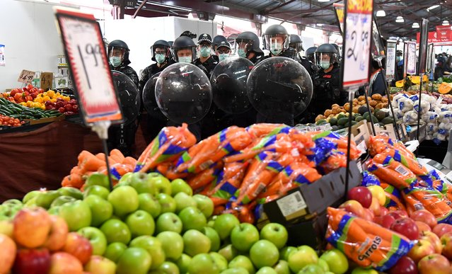 Riot police clear Melbourne's Queen Victoria Market of anti-lockdown protesters during a rally on September 13, 2020, amid the ongoing COVID-19 coronavirus pandemic. Melbourne continues to enforce strict lockdown measures to battle a second wave of the coronavirus. (Photo by William West/AFP Photo)