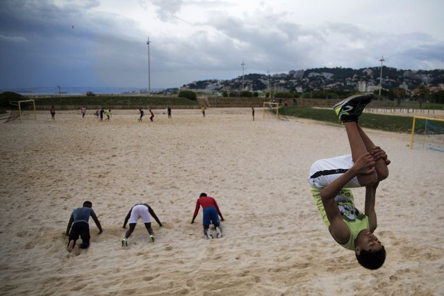 Yannis does a flip while practicing freerunning at a beach in Marseille, southern France, Saturday, May 16, 2020. Beaches in Marseille have become partially accessible since the lifting of lockdown measures meant to prevent the spread of coronavirus. (Photo by Daniel Cole/AP Photo)
