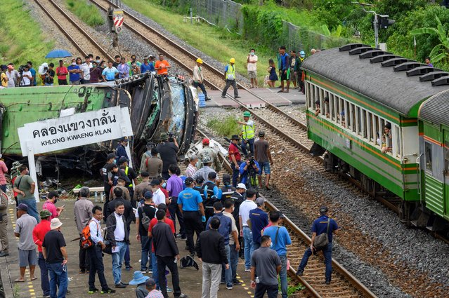 Officials and onlookers gather near the wreckage of an overturned bus involved in a deadly collision with a train next to Khlong Kwaeng Klan railway station in Chachoengsao province, east of the Thai capital Bangkok, on October 11, 2020. (Photo by Mladen Antonov/AFP Photo)