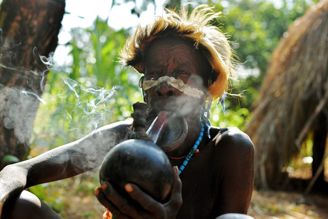 """An elderly woman from the Suri tribe smokes a pipe in Ethiopia's southern Omo Valley region near Kibbish on September 25, 2016. The Suri are a pastoralist Nilotic ethnic group in Ethiopia. The construction of the Gibe III dam, the third largest hydroelectric plant in Africa, and large areas of very """"thirsty"""" cotton and sugar plantations and factories along the Omo river are impacting heavily on the lives of tribes living in the Omo Valley who depend on the river for their survival and way of life. Human rights groups fear for the future of the tribes if they are forced to scatter, give up traditional ways through loss of land or ability to keep cattle as globalisation and development increases. (Photo by Carl De Souza/AFP Photo)"""