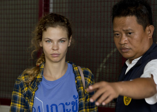 A police officer escorts Anastasia Vashukevich from a detention center in Pattaya, south of Bangkok, Thailand, Wednesday, February 28, 2018, after she was arrested Sunday in the Thai resort city of Pattaya while giving s*x lessons to Russian tourists. Vashukevich told The Associated Press from a police van Wednesday that she fears for her life, and wants to exchange information on alleged Russian ties to U.S. President Donald Trump's campaign for her own personal safety. (Photo by Gemunu Amarasinghe/AP Photo)