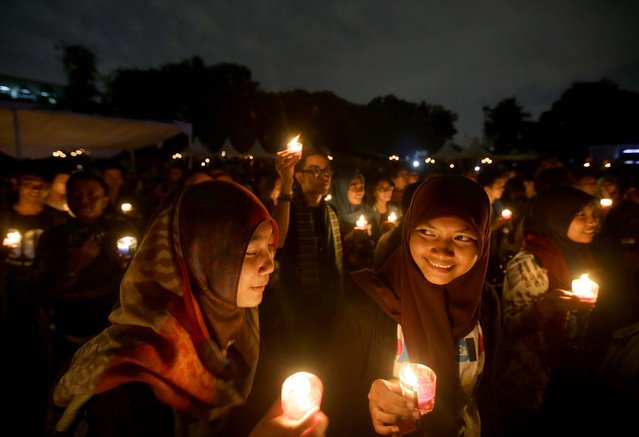 "Muslim women light candles during the ""EarthHour"" in Jakarta, Indonesia, on March 23, 2013. Hundreds of people observed the global event that encourages people to turn off their lights for 60 minutes. (Photo by Dita Alangkara/Associated Press)"
