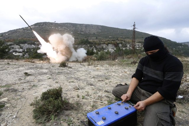 A rebel fighter fires a Grad long distance shell towards forces loyal to Syria's president Bashar Al-Assad located in the city of Jableh at the Syrian coast, from Jabal al-Akrad area in Syria's northwestern Latakia province December 4, 2014. (Photo by Alaa Khweled/Reuters)
