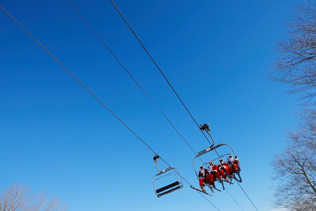 Skiers and snowboarders dressed as Santa Claus ride a chair lift to participate in a charity run down a slope at Sunday River Ski Resort in Newry, Maine December 7, 2014. (Photo by Brian Snyder/Reuters)