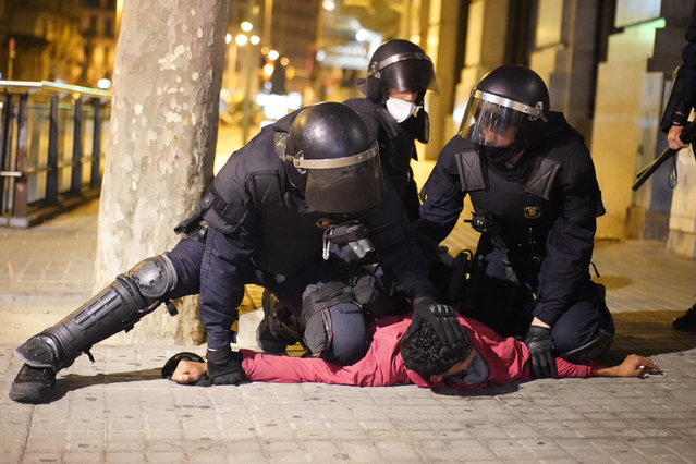 A demonstrator is detained by police officers during clashes in downtown Barcelona, Spain, Friday, October 30, 2020. (Photo by Joan Mateu/AP Photo)
