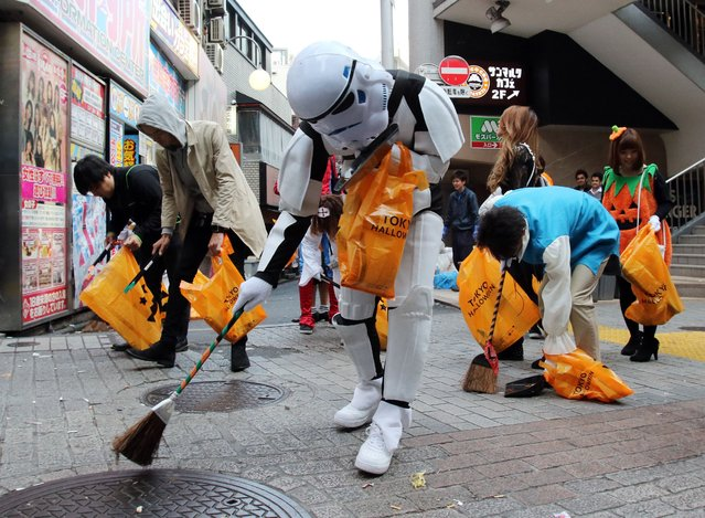 People in costumes collect garbage on the street after their Halloween party at Tokyo's Shibuya fashion district on November 1, 2015.  Hundreds of volunteers collected garbage to make an art object for the Tokyo Design Week art event. (Photo by Yoshikazu Tsuno/AFP Photo)