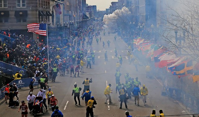 Moments after the first explosion near the finish line of the Boston Marathon, smoke is seen in the background where a second explosion occurred. (Photo by David L. Ryan/The Boston Globe)