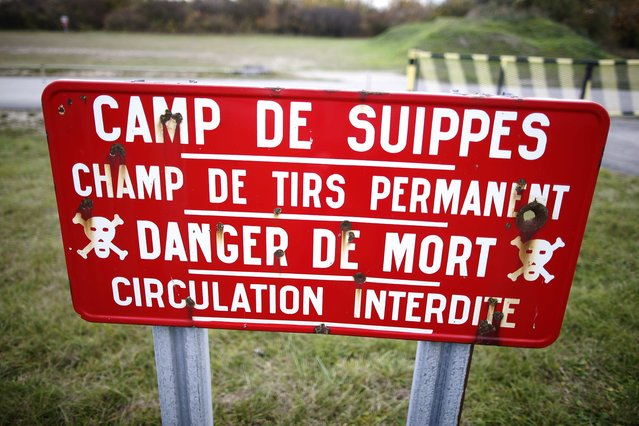 A warning road sign is posted near the entrance of the Camp de Suippes, near Reims, France, November 3, 2015. During World War One many French villages were destroyed, some never to be reconstructed because they were heavily damaged or because the nearby fields contain unexploded munitions, mines, explosives and artillery shells. The Camp de Suippes, opened in 1922, is a French Army training area for live artillery firing exercises, and closed to the public. (Photo by Charles Platiau/Reuters)