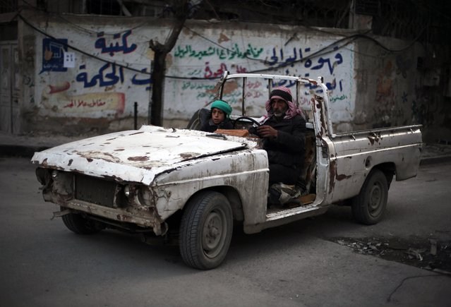 A Syrian man and his son drive in vehicle battered by years on conflict in the rebel-held area of Douma, east of the capital Damascus, on November 10, 2015. (Photo by Amer Almohibany/AFP Photo)