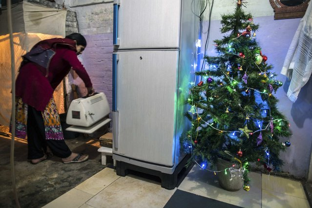 A woman works in her kitchen beside a Christmas tree in a Christian slum in Islamabad on Christmas eve December 24, 2014. (Photo by Zohra Bensemra/Reuters)