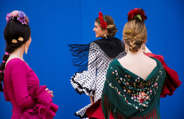 Women wearing traditional costumes chat during the first day of the April Fair celebrations in Sevilla, southern Spain, 15 April 2018. (Photo by Raúl Caro Cadenas/EPA/EFE)