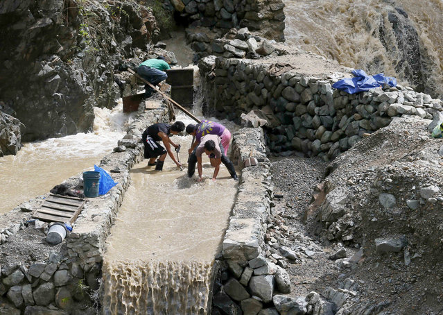 Small scale miners take advantage of the muddy waters from the mountains brought about by super Typhoon Haima as they prepare to pan for gold at Tuba township, Benguet province in northern Philippines Friday, October 21, 2016. Super Typhoon Haima slammed into the northeastern Philippine coast late Wednesday with ferocious winds and rain that rekindled fears and memories from the catastrophe wrought by Typhoon Haiyan in 2013. (Photo by Bullit Marquez/AP Photo)