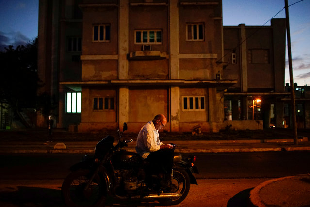 A man sits on his Russian-made Ural motorbike as he checks the Internet at a hotspot in Havana, Cuba on December 19, 2017. (Photo by Alexandre Meneghini/Reuters)