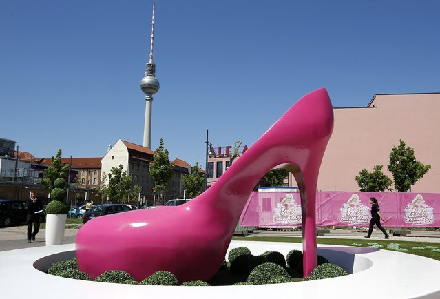 "A giant shoe is pictured outside a life-size ""Barbie Dreamhouse"" of Mattel's Barbie dolls in Berlin, May 15, 2013. The life-sized house, covering about 1,400 square metres offers visitors to try on Barbie's clothes in her walk-in closet, tour her living room and her kitchen. (Photo by Fabrizio Bensch/Reuters)"