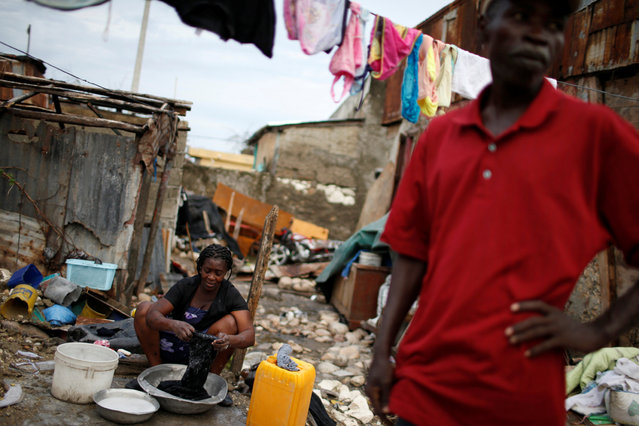 A woman washes clothes amidst the rubble of her destroyed house after Hurricane Matthew hit Jeremie, Haiti, October 19, 2016. (Photo by Carlos Garcia Rawlins/Reuters)