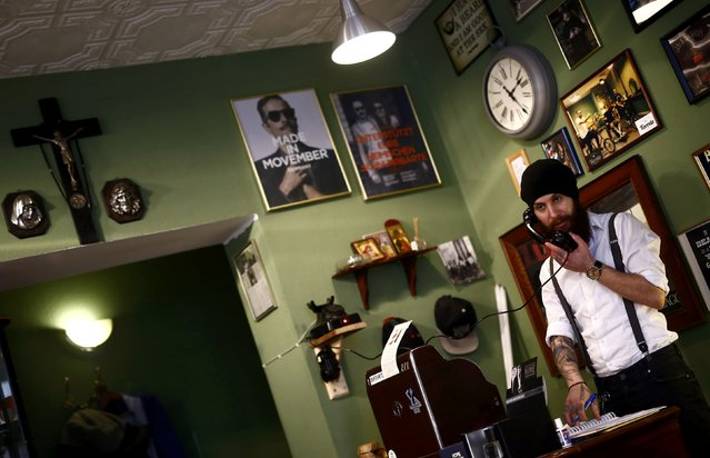 "Alex ""Torreto"" Vellios, a 26-year old Greek-born barber takes a call for an appointment on his vintage phone at his Torreto barber shop in Frankfurt January 6, 2015. (Photo by Kai Pfaffenbach/Reuters)"