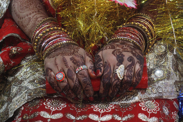 A bride holds her purse with hands that are decorated with henna patterns, during a mass marriage ceremony held in Karachi January 2, 2015. (Photo by Athar Hussain/Reuters)