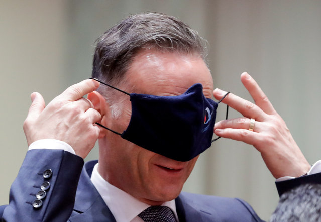 German Foreign Minister Heiko Maas puts his protective mask on his eyes while he attends a meeting of EU foreign ministers at the European Council building in Brussels, Belgium on July 13, 2020. (Photo by Stephanie Lecocq/Pool via Reuters)