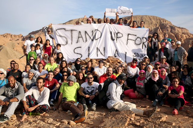 """Hikers hold a banner that reads """"Stand up for Sinai"""" as they reach the top of Naqba Rum area in South Sinai, Egypt, November 20, 2015. (Photo by Asmaa Waguih/Reuters)"""