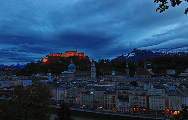"""Castle in the Setting Sun"". The night is approaching, so is a storm. Suddenly, a beam of light from the setting sun illuminates the Hohensalzburg Fortress, dying it orange for just seconds, giving birth to this miraculous image. (Photo was taken in May, 2012). Location: Salzburg,  Austria. (Photo and caption by Feng Xue/National Geographic Traveler Photo Contest)"