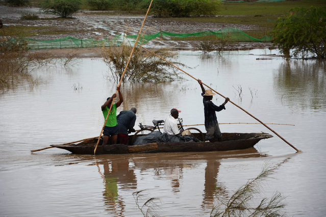 Flood victims make their way to a relief station with their salvaged belongings at Bangula, Malawi, in the southern district of Nsanje, Sunday January 18, 2015. Flooding in Malawi has killed more than 176 people, displaced at least 200,000 others, left homes and schools submerged in water and roads washed away by the deluge in the southern African country. (Photo by Thoko Chikondi/AP Photo)