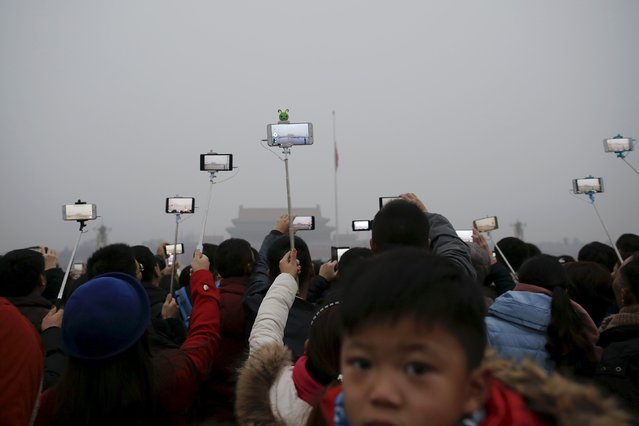 "People film with their cameras during a flag-raising ceremony amid heavy smog at the Tiananmen Square, after the city issued its first ever ""red alert"" for air pollution, in Beijing December 9, 2015. (Photo by Damir Sagolj/Reuters)"