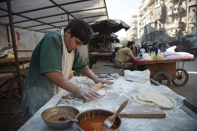 A Syrian boy prepares manakish in the rebel-held side of the northern embattled city of Aleppo on October 27, 2016. Regime forces backed by ally Russia have waged an aerial and ground assault since late September to recapture eastern Aleppo, killing hundreds of civilians and destroying infrastructure including hospitals. (Photo by Karam Al-Masri/AFP Photo)
