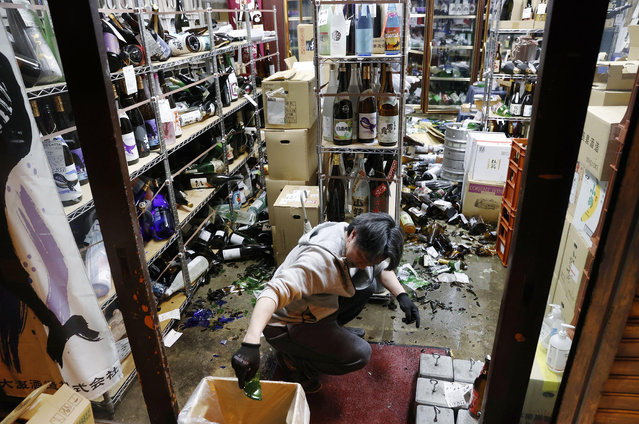 A liquor shop's manager clears the damaged bottles following an earthquake in Fukushima, northeastern Japan Saturday, February 13, 2021. The Japan Meteorological Agency says a strong earthquake has hit off the coast of northeastern Japan, shaking Fukushima, Miyagi and other areas. (Photo by Jun Hirata/Kyodo News via AP Photo)