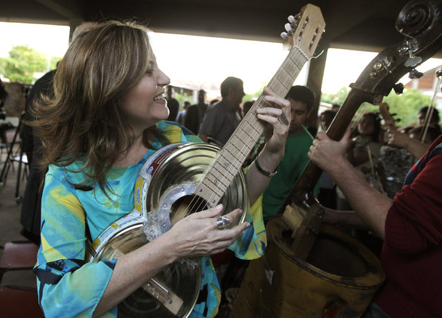Renowned Paraguayan classical guitarist, Bertha Rojas, plays an instrument made from recycled food tins by craftsman Nicolas Gomez, during a visit to the Orchestra of Recycled Instruments of Cateura in Cateura, near Asuncion, May 9, 2013. (Photo by Jorge Adorno/Reuters)