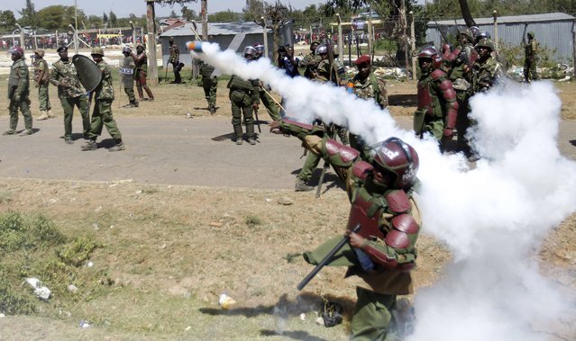 A riot policeman throws a teargas canister to disperse demonstrators during protests to oust Narok county Governor Samuel Tunai in Narok, Kenya, January 26, 2015. (Photo by Thomas Mukoya/Reuters)
