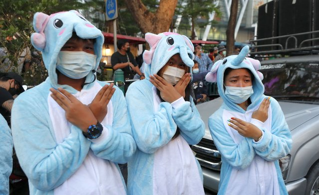 Pro-democracy protesters wearing elephant custom raise a three-finger salute, a symbol of resistance during protest in Bangkok, Thailand, Tuesday, February 23, 2021. Protesters gathered to call for fairness for low-ranking police after the opposition parties accused PM Prayuth Chan-ocha and deputy PM Prawith Wongsuwan of promoting a culture of patronage and bypassing the normal system inside the police forces during the parliament's censure debate last week. (Photo by Sakchai Lalit/AP Photo)