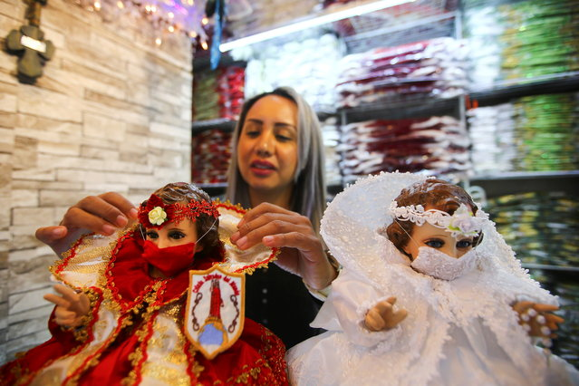 A saleswoman adjusts the suit of a dressed-up doll representing baby Jesus wearing a face mask to promote the use of masks, as a precautionary measure amid the coronavirus disease (COVID-19) outbreak before Christmas celebration, inside a store in Mexico City, Mexico, December 9, 2020. (Photo by Edgard Garrido/Reuters)