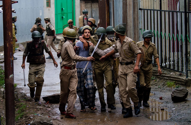 Indian police officers arrest a Kashmiri boy protesting during curfew in Srinagar, India, Saturday, July 20, 2013. Authorities in Indian-administered Kashmir Saturday decided to extend a curfew following violent protests over the deaths of four people in shooting by the paramilitary police. Although the situation remained largely peaceful on Saturday, clashes between stone-throwing mobs and security forces until late Friday left 59 people, including 49 police and paramilitary, injured, a police spokesman said. (Photo by Dar Yasin/AP Photo)
