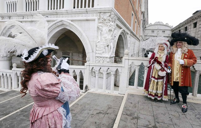 A reveller takes a picture with her mobile phone of friends in front of the Ponte dei Sospiri (Bridge of Sighs) during the first day of the  Venice Carnival, February 1, 2015. (Photo by Stefano Rellandini/Reuters)