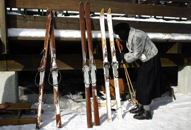 "A competitor checks her vintage skis and poles at the ""Nostalgic Ski Race"" in the western town of Neuastenberg February 8, 2015. (Photo by Ina Fassbender/Reuters)"