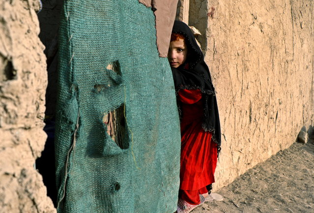 A young Afghan Internally Displaced Person (IDP) stands outside a temporary shelter in an IDP camp in Kabul, Afghanistan, December 21, 2015. According to UN Refugee Agency (UNHCR) figures, the number of internally displaced Afghans was 683,000 by mid-2014, a number expected to climb to 900,000 by the end of 2015, as unrest continues in the country after several offensives by the Taliban in various provinces leading to large Afghan National Army (ANA) losses. (Photo by Hedaytullah Amid/EPA)