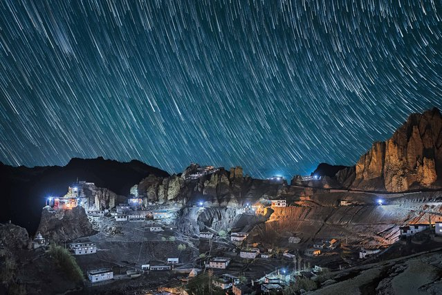 The village of Dhankar in the Spiti Valley, Himachal Pradesh, northern India illuminated by streetlights as a sky of star trails fill the nights sky. (Photo by Grey Chow/Caters News Agency)