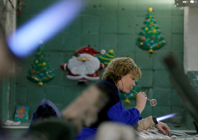 """An employee blows a glass sphere for Christmas and New Year decoration at the """"Yolochka"""" (Christmas tree) factory, which has been producing glass decorations and toys for the festive season since 1848, in the town of Klin outside Moscow, Russia, November 24, 2016. (Photo by Maxim Zmeyev/Reuters)"""